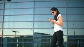 Lyckad affärskvinna eller entreprenör med att gå för smartphone som är utomhus-