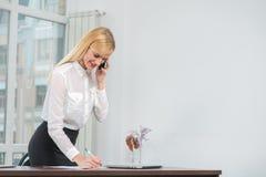 Lyckad affärskvinna eller entreprenör som tar anmärkningar och talkin arkivfoto