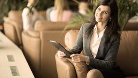 Lyckad affärskvinna med dokument som sitter i en stol i en lobby av ett modernt kontor royaltyfri fotografi
