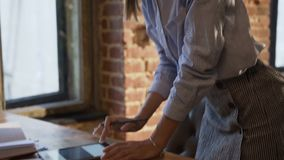 Lyckad affärskvinna som arbetar genom att använda minnestavlan på kontoret Fokuserad ung affärsdam i exponeringsglas med långt hå arkivfilmer