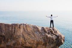 Lyckad affärsman för frihet över ett högt berg Royaltyfri Foto