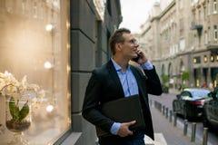 Lyckad affärsman i dräkt med bärbara datorn som talar på telefonen och ler i staden fotografering för bildbyråer