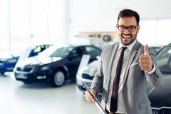 Lyckad affärsman i en bilåterförsäljare - försäljning av medel till kunder royaltyfri bild