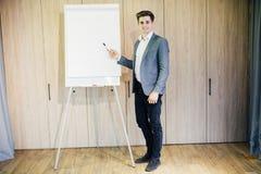 Lyckad affärsman med ett flipdiagram i en presentation i modernt kontor royaltyfri bild