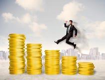 Lyckad affärsman som hoppar upp på pengar för guld- mynt Arkivfoto