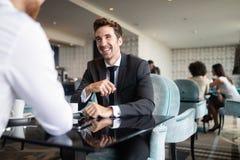 Lyckad affärsman som ler, medan diskutera med partnern under att möta på kaffeavbrottet arkivfoton