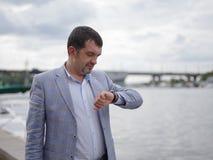 Lyckad affärsman som ser klockan på hans hand på den stads- bakgrunden för burlapmynt för bakgrund öppnar fritt fullt guld- trevl arkivbild