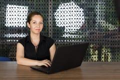 Lyckad affärskvinna som arbetar på bärbara datorn Royaltyfria Bilder