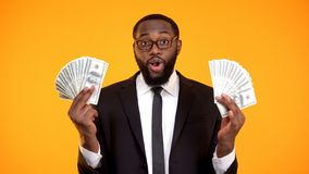 Lyckad afrikansk aff?rsman i glas?gon som visar grupper av kassa, vinst royaltyfri bild