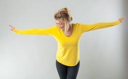 Lyckad blond kvinna som ler med armar som öppnas för teatergest Royaltyfria Bilder