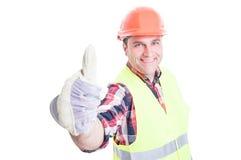 Lyckad byggmästare som ler upp och visar tummen Royaltyfri Foto