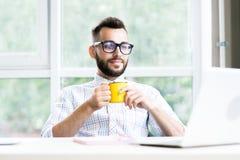 Lyckad entreprenör Drinking Coffee i regeringsställning arkivfoton