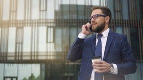 Lyckad företagsägare som talar på telefonen som dricker kaffeanseende på stadsgatan arkivfilmer