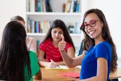 Lyckad fransk kvinnlig student som lär med gruppen av studenter royaltyfri foto