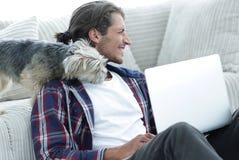 Lyckad grabb och hans favorit- husdjur i en hemtrevlig vardagsrum royaltyfria bilder