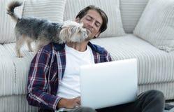 Lyckad grabb och hans favorit- husdjur i en hemtrevlig vardagsrum arkivbild