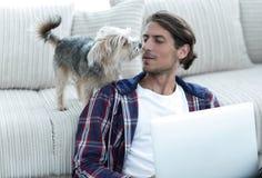 Lyckad grabb och hans favorit- husdjur i en hemtrevlig vardagsrum arkivfoto