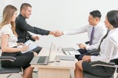 Lyckad handskakning av två affärsmän på kontoret Arkivfoto