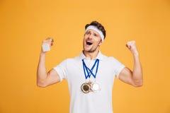 Lyckad idrottsman med tre medaljer som ropar och firar seger Royaltyfri Fotografi