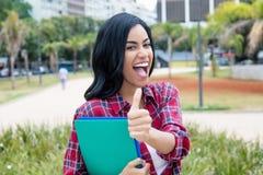 Lyckad infödd latin - amerikansk visningtumme för kvinnlig student royaltyfri bild