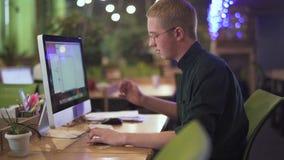 Lyckad kontorsarbetare i en berömd affärsmitt Ung fundersam man i exponeringsglas som framme sitter på hans arbetsplats lager videofilmer