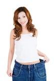 Lyckad kvinna i för stor jeans Fotografering för Bildbyråer