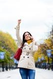 Lyckad kvinna på mobiltelefonappell i höst Royaltyfri Fotografi