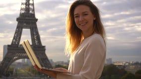Lyckad kvinna som bläddrar vid bärbara datorn med Eiffeltornbakgrund och ser kameran lager videofilmer