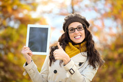 Lyckad kvinna som rymmer den digitala minnestavlan i höst Royaltyfri Foto