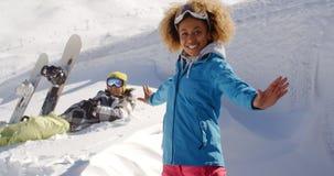 Lyckad kvinnlig skidåkare bredvid man i snö royaltyfri bild
