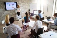 Lyckad lycklig grupp människor som lär programvaruteknik och affär under presentation royaltyfri bild