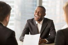 Lyckad lycklig svart manlig kandidat som får hyrd, fånget ett jobb arkivbilder