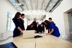 Lyckad mång- folkgrupp av iklädd lyxig företags kläder för arkitekter som tillsammans arbetar under förhandsmöte, royaltyfri fotografi