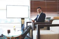 Lyckad man i läs- eBook för elegant dräkt på hans digitala minnestavla arkivbilder