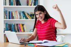 Lyckad mexikansk kvinnlig student som lär på datoren arkivbilder