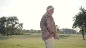 Lyckad mogen golfaregolfspel för stående på härlig kurs Säkert mananseende i soligt sommarväderanseende stock video