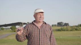 Lyckad mogen man med ett golfklubbanseende på en golfbana i bra soligt väder Hög golfare för stående sport arkivfilmer