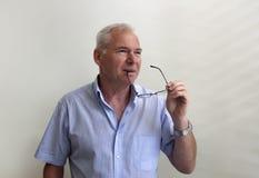 Lyckad mogen man som rymmer exponeringsglas i hans hand royaltyfria foton