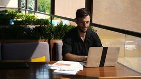 Lyckad ordförande som använder bärbara datorn och dokument på kafét lager videofilmer
