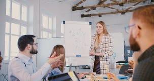 Lyckad positiv Caucasian affärslagledarekvinna som förklarar marknadsföringsdiagrammet, multietniskt kollegalag på seminariet arkivfilmer