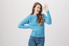 Lyckad säker caucasian kvinna som ler, medan stå med handen på midjan och lyfta en annan arm med godkännande eller Arkivbilder