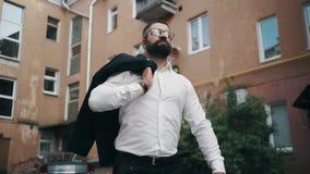 Lyckad skäggig affärsman med exponeringsglas som går ner gatan med ett omslag på hans skuldra stock video