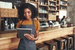 Lyckad små och medelstora företagägare som använder den digitala minnestavlan i hennes kafé royaltyfri foto