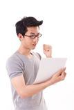 Lyckad smart nerd- eller geekstudentman som ser dokumentet Arkivbilder