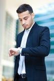 Lyckad stilig affärsman som ser hans klocka Arkivbild