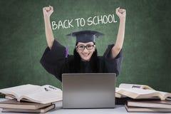 Lyckad student med akademikermössan tillbaka till skolan Royaltyfri Foto