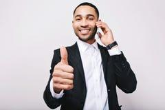 Lyckad tid av den unga stiliga mannen i den vita skjortan, svart omslag som uttrycker positivity till kameran på vit bakgrund royaltyfri bild