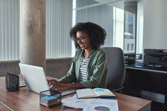 Lyckad ung affärskvinna som använder bärbara datorn royaltyfri foto
