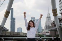 Lyckad ung asiatisk affärskvinna som lyfter händer på stads- byggnadsstadsbakgrund royaltyfria bilder