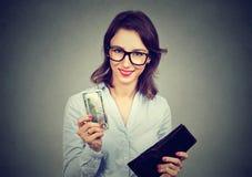 Lyckad ung kvinna som betalar för henne erbjudande kassa för hållande plånbok Royaltyfri Foto